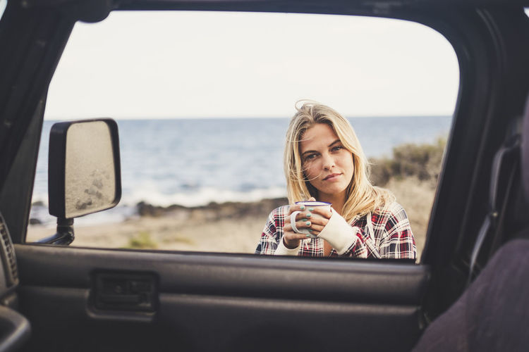 Portrait Of Young Woman Holding Coffee Cup By Car Against Sky At Beach