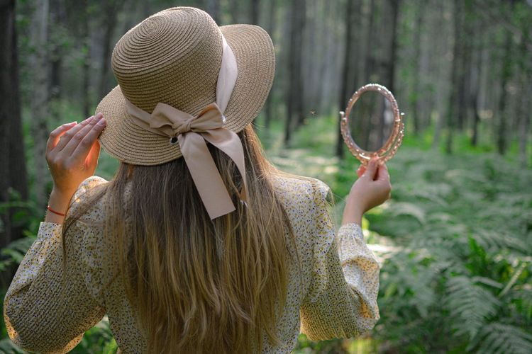 Rear view of woman holding hand mirror standing in forest