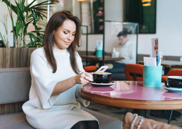 Attractive young brunette woman in white casual dress with cup of coffee using mobile phone in cafe