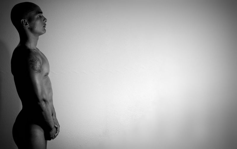 Side view of sensuous naked man standing against white wall