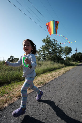 Our daughter tried her best to fly our new kite California Candid Casual Clothing Child Childhood Children Only Day Full Length Girls Grass Happiness Leisure Activity Lifestyles One Person Outdoors Plant Playing Portrait Real People Sky Smiling Tree USA Young Adult Young Women