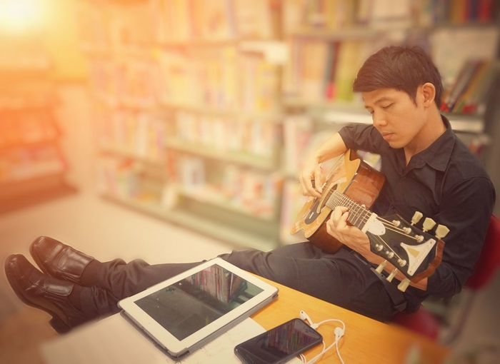 Full length of man playing guitar while sitting in library