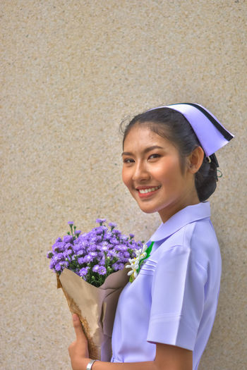 Smiling Young Nurse With Bouquet Standing Against Wall