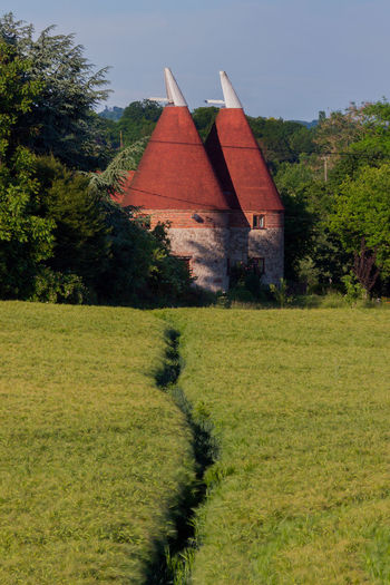 Oast House, Garden Of England, Kent, England. Architecture Sky Built Structure Nature No People Plant Hops Beer Brewing Iconic Buildings Vivid International Getty Images EyeEm Gallery Travel Destinations Tourism Sunrise Countryside Rural Scene History Grass Building Exterior Building Green Color Tree Landscape Day Field House Land Growth Tranquil Scene Environment Outdoors