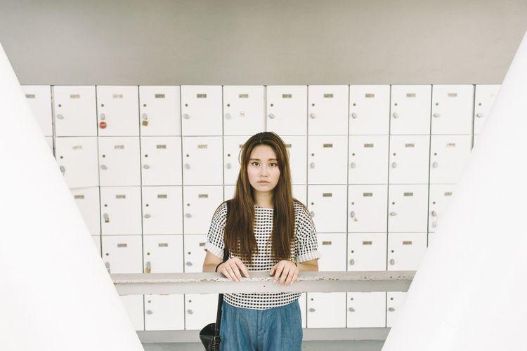 Portrait Of Woman Standing Against Lockers