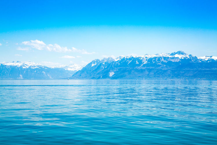 Scenic view of snowcapped mountains by sea against blue sky