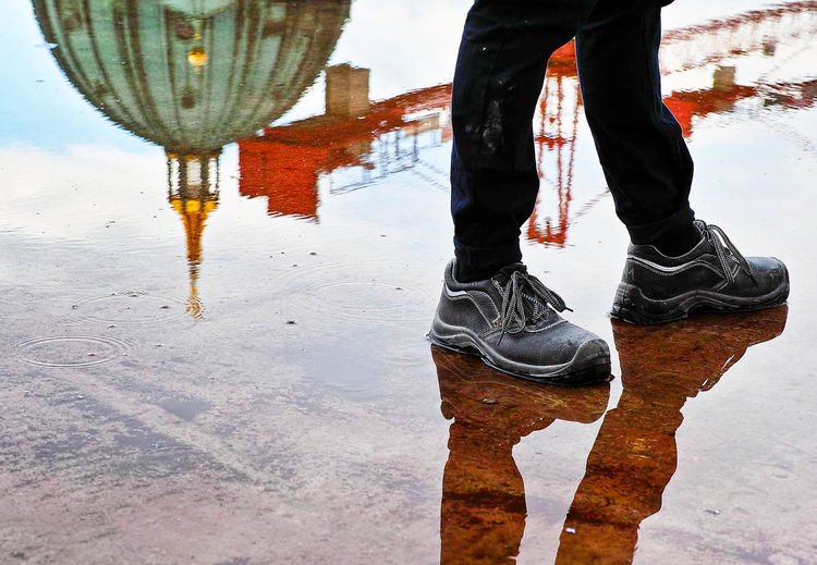 Low section of man walking by berlin cathedral reflection on walkway in rainy season
