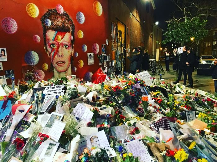 Floral tributes are placed by the David Bowie Mural in Brixton on February 4, 2016 in London Fans Music David Bowie Starman Flowers Night Memorial Legend Remembering