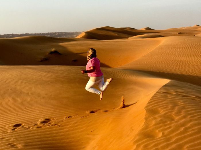 Woman Jumping Over Sand Dune Against Sky During Sunset