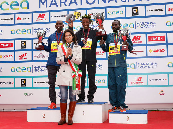 Rome, Italy - April 2, 2017: The mayor of Rome Virginia Raggi on stage with the top three finishers in the men's race of the 23rd marathon in Rome. At the center of Tola Shura Kitata first place. To his right, Dominic Ruto Kipngetich, second place. To his left, Bitok Benjamin Kipngetic, third place. Athletes Athletes; Award; Awards Color; Day Ethiopian; Kenyan; Marathon Medal Outdoors Podium; Rome Marathon Rome Marathon 2017 Rome Marathon 23rd Runners; Winners