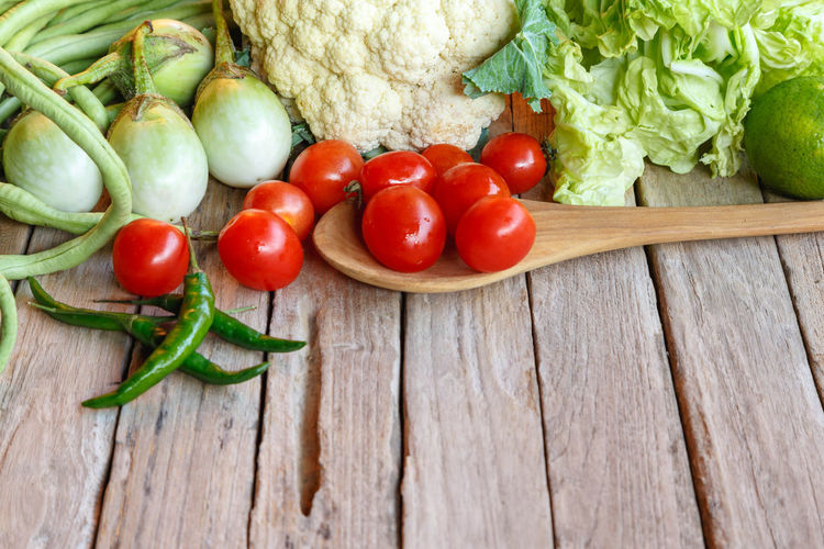 Tomatoes and vegetables on wood