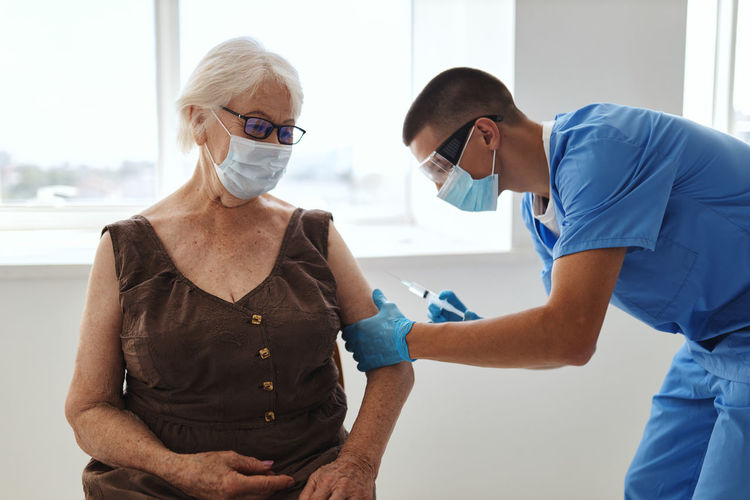 Doctor injecting vaccine to patient