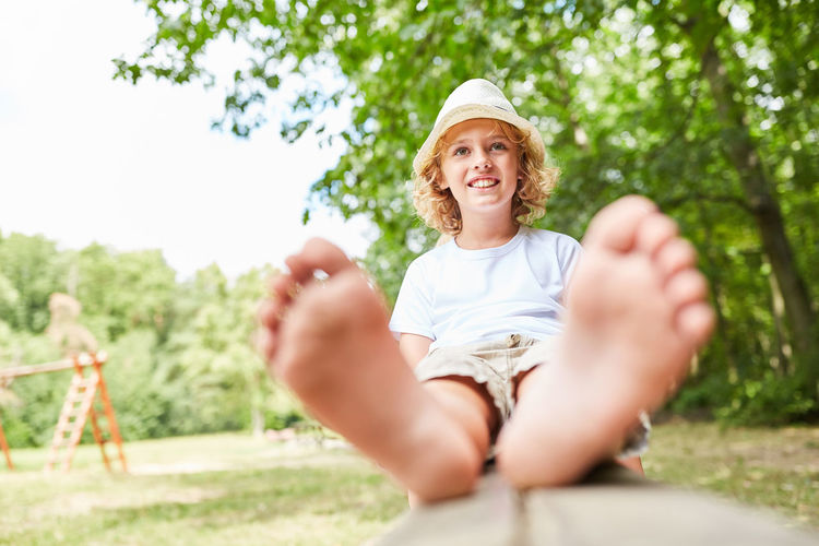 portrait of smiling girl sitting on plant against trees barefoot Boy Break Calm Carefree Casual Clothing Child Childhood Children Day Faineance Feet Foot Front View Garden Happy Holiday Idle Innocence Kids Leisure Leisure Activity Lifestyle Lifestyles Looking At Camera Luck Men Nature One Person Outside Park Peaceful People Plant Portrait Real People Recreation  Relaxation Relaxed Rest Selective Focus Silence Sit Sitting Smile Smiling Summer Tree Vacation