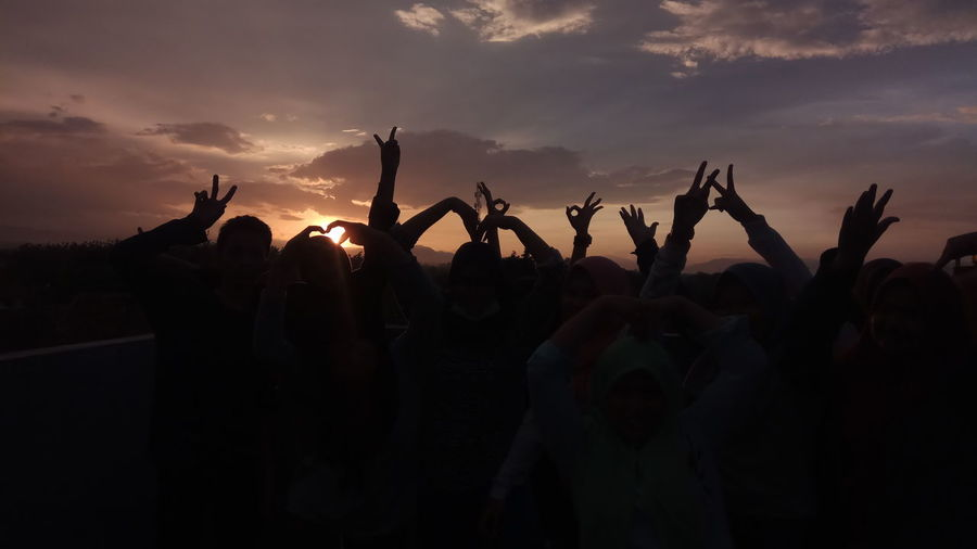 Silhouette friends with arms raised standing on field against cloudy sky during sunset