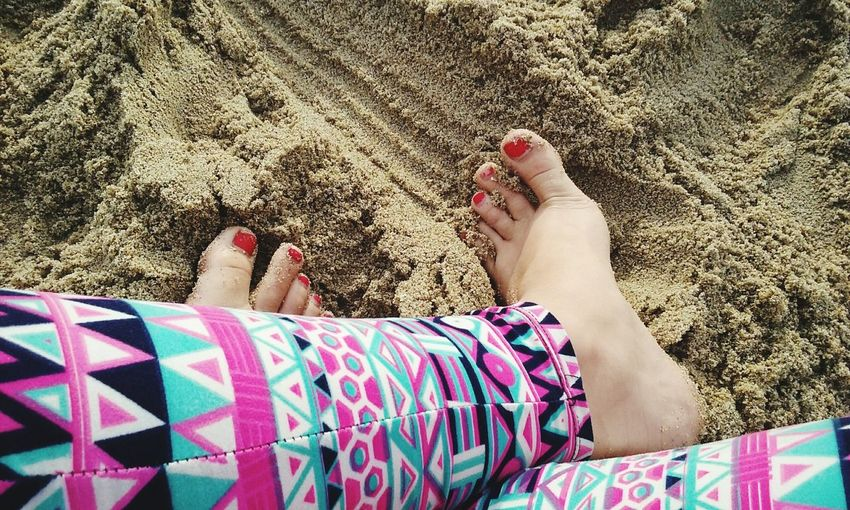 Close-up of legs on sand