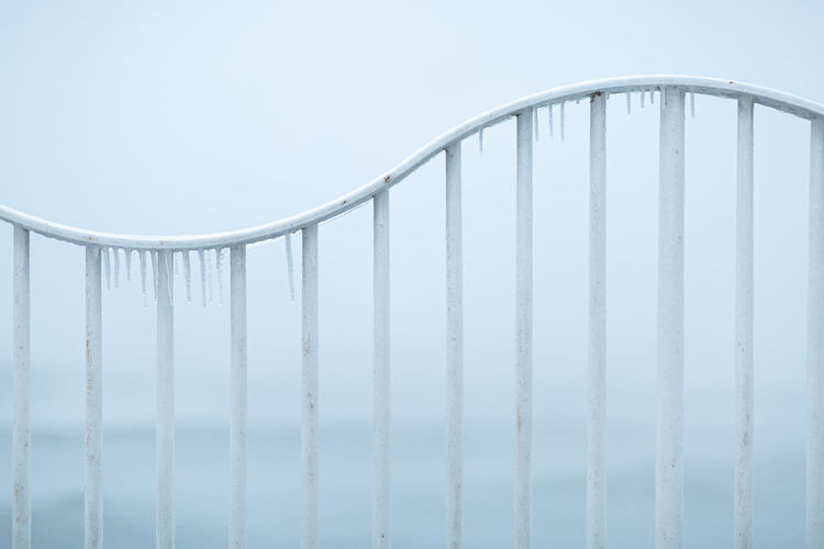Low angle view of railing against sky during winter