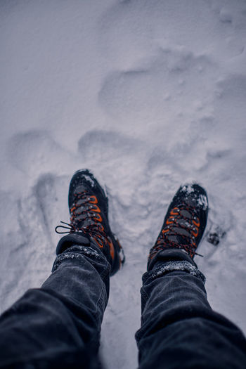First person view on a man's legs with a black jeans and black and orange hiking boots on snow.