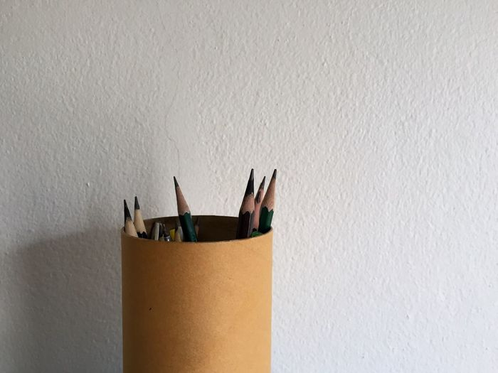 Close-up of pencil on table against wall