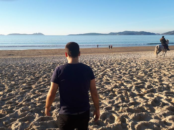 Rear view of man standing at beach against clear sky