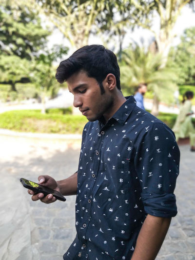 Young man using phone while standing at park