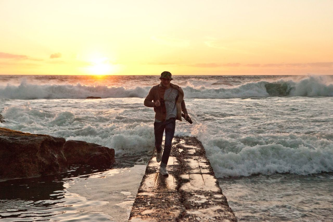 Man running on pier against sea waves at sunset