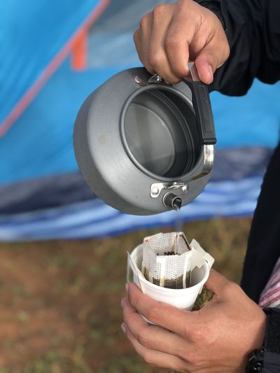 Cropped hand of person pouring hot water in tea cup at campsite