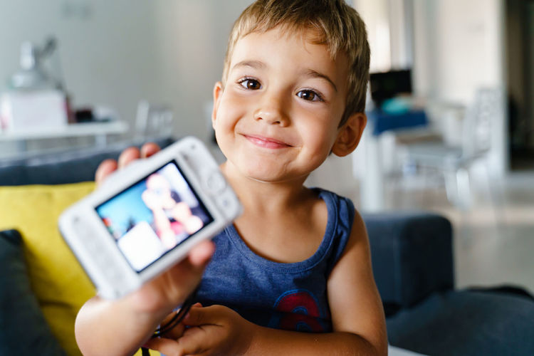 Portrait of boy holding mobile phone at home