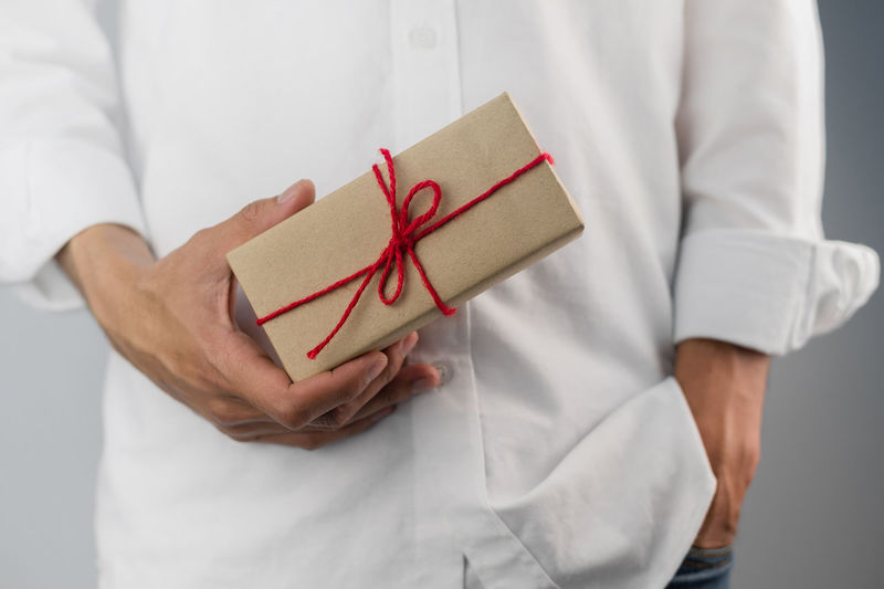 Midsection of man holding paper box