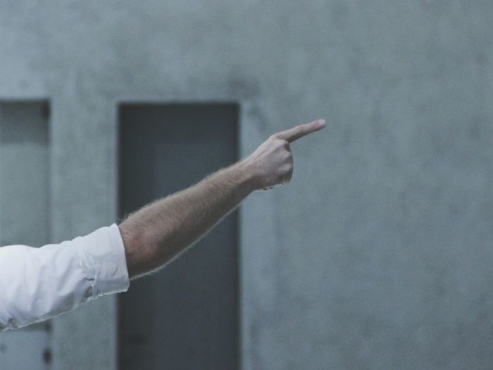 Cropped image of man pointing against wall