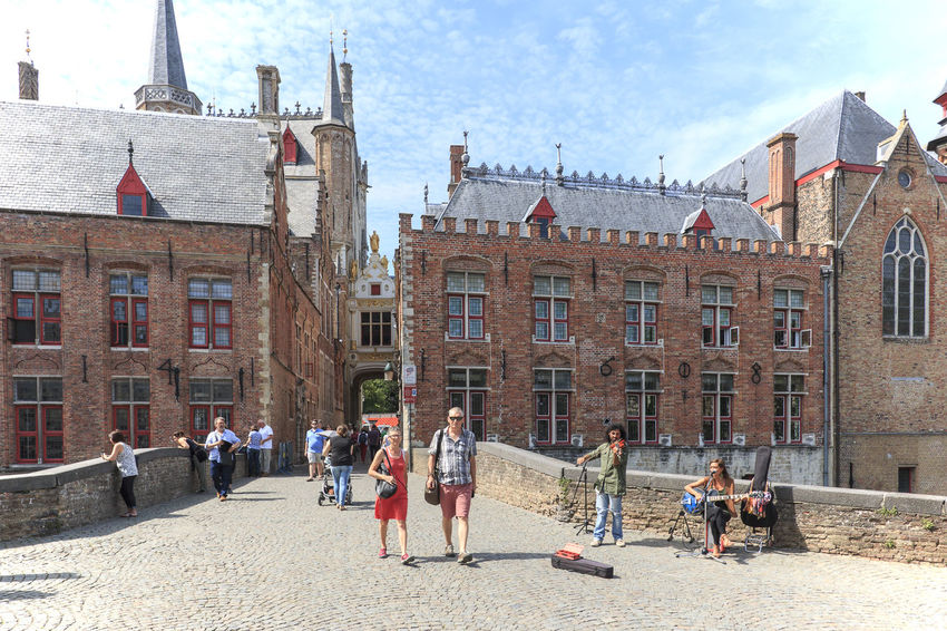 Bruges, Belgium - July 7, 2017: Tourists walking in the narrow streets in the center of Bruges. Bruges is also called the Venice of the North due to the numerous canals Beer Belgium Brugge Chocolate Dijver Canal Duvel Flanders Panoramic View Provinciaal Hof West Flanders Aerial View Belfry Tower Bikes Bruges Europe Flower French Fries Holland Market Square Medieval Town Mussels