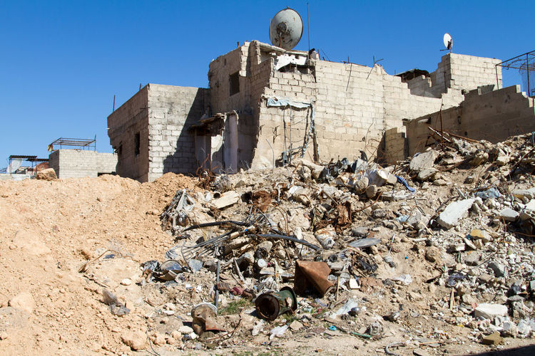 Damaged building in syria against clear blue sky