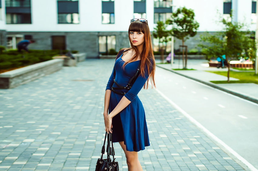 Young attractive woman with long legs with long hair in a blue elegant dress with a sword belt In sunglasses, strolls in a European modern courtyard, a warm summer day Adult Architecture Beautiful Woman Blue Building Exterior Built Structure Casual Clothing City Day Focus On Foreground Full Length Lifestyles Long Hair One Person Outdoors People Purse Real People Street Young Adult Young Women Business Stories