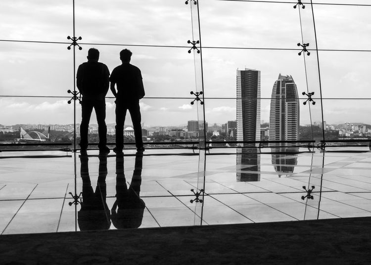 Silhouettes of two men standing inside the Putrajaya International Convention Centre looking at the cityscape of Putrajaya through glass walls Adults Only Architecture B&w Black And White Blackandwhite Buildings City Cityscape Glass Wall Grid Looking Out Of The Window Men Putrajaya International Convention Centre Reflections Silhouettes Sky Standing Streetphotography Two People Urban Urbanphotography