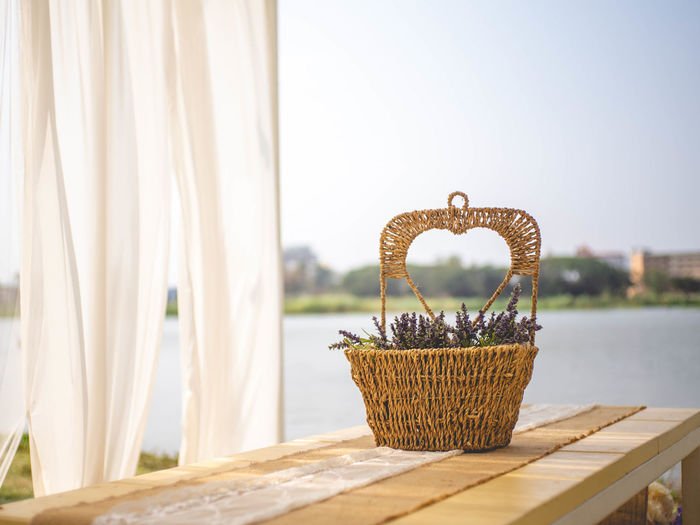 Close-up of wicker basket on table against clear sky
