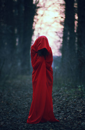 Person in red cloak in forest