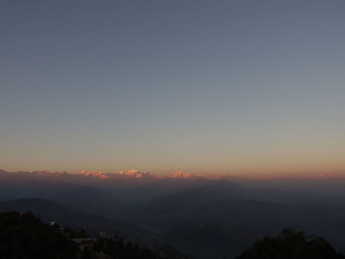 Scenic view of mountains against clear sky at sunset