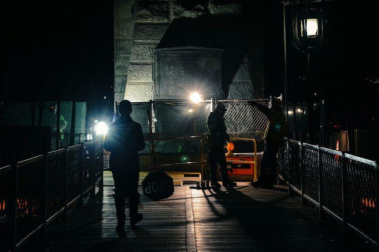 People Walking On Brooklyn Bridge At Night