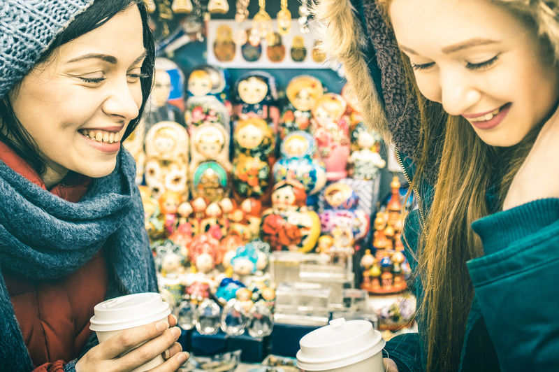 Close-up of smiling woman drinking coffee at store