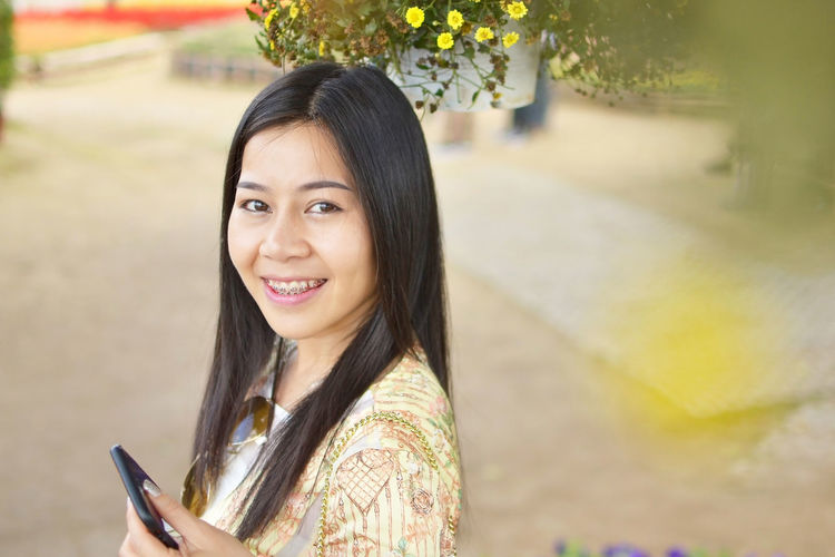 Portrait of smiling woman using mobile phone in city