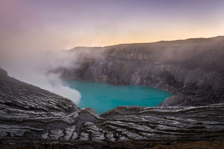 View of Kawah Ijen mountain and lake in Indonesia Nature Kawah Ijen Volcano INDONESIA East Java Blue Crater Landscape Nature Lake Sunrise Rock Danger Smoke Gas Mountain Beautiful Mist Fog ASIA Scenic Mask Acid Adventure