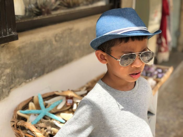 Portrait of boy wearing sunglasses and hat standing outdoors