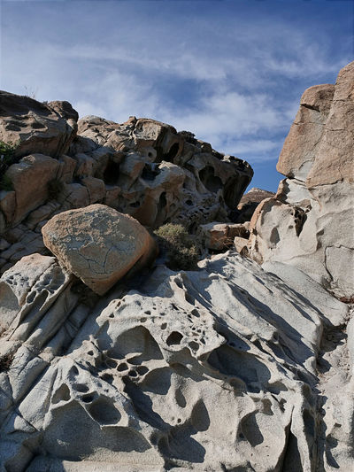 Low angle view of rock formation on beach against sky