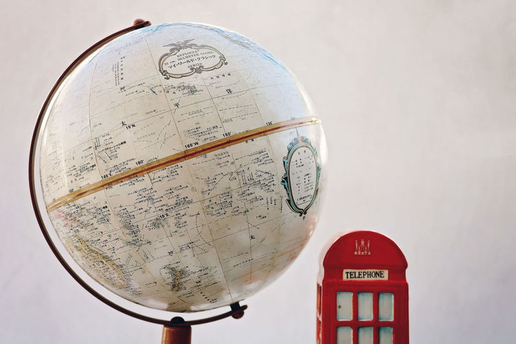 Close-up of globe by telephone booth against wall