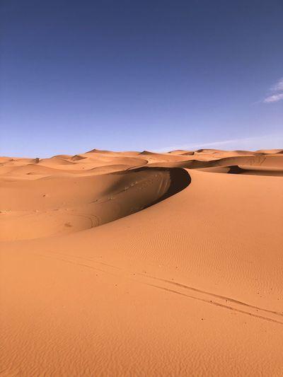 Sand dunes in sahara desert against clear blue sky