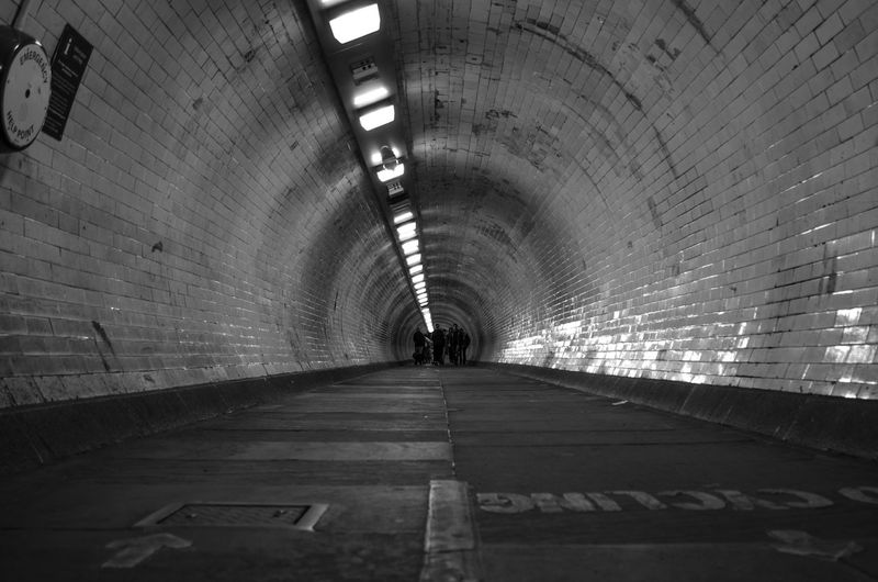 People walking in illuminated tunnel