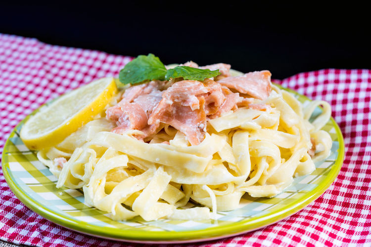 Close-up of tagliatelle with salmon on table against black background