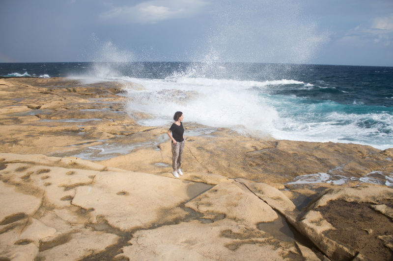 Sea Water Full Length One Person Motion Land Nature Adult Sport Wave Young Adult Beach Standing Day Rock Aquatic Sport Surfing Beauty In Nature Looking At View Travel Destinations Holiday Moments