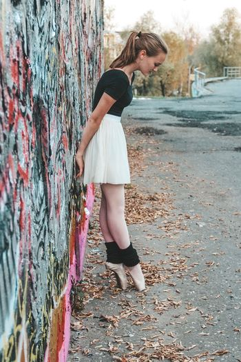 Side view of young woman dancing on road by wall