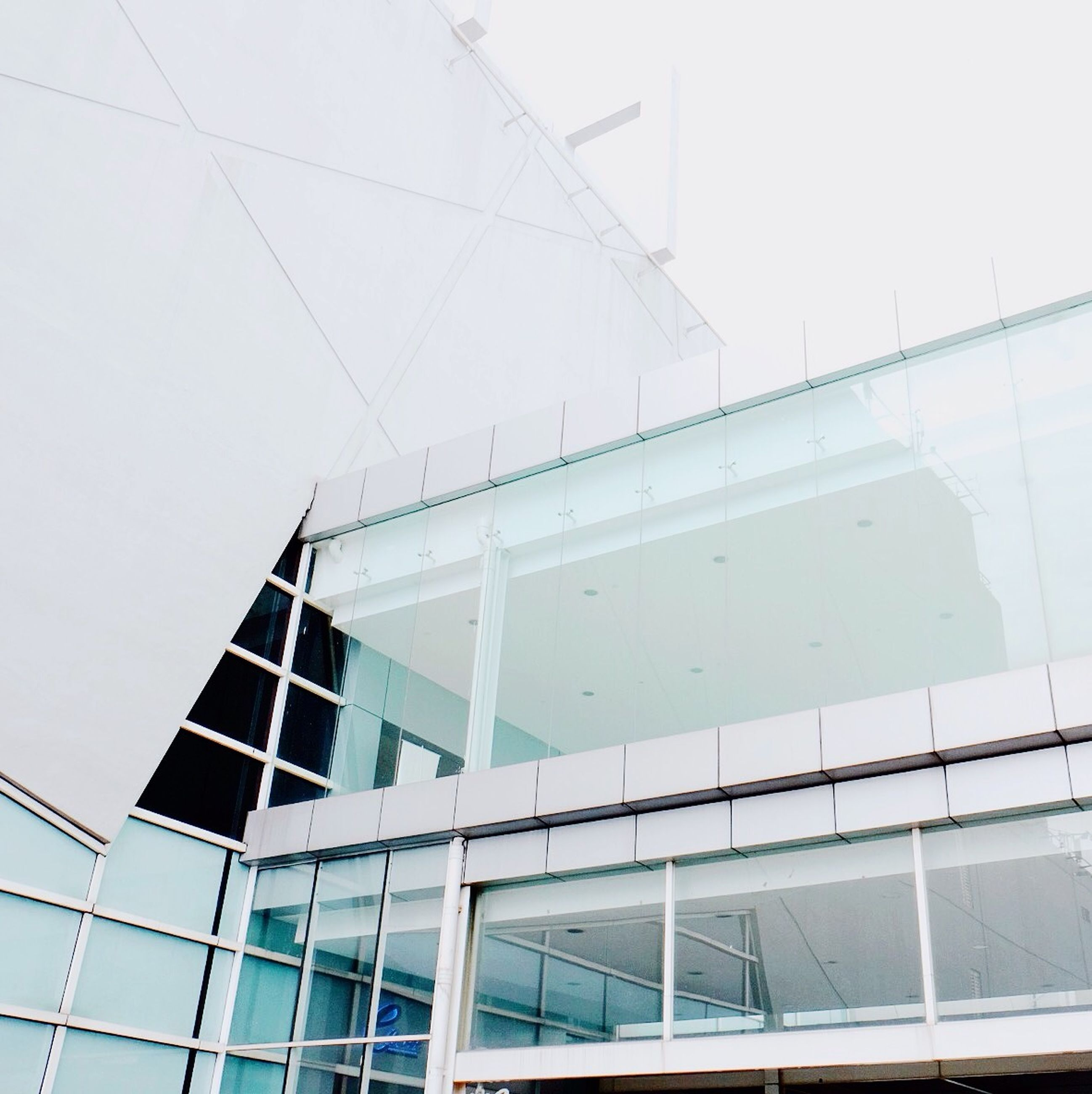 architecture, built structure, building exterior, low angle view, modern, glass - material, reflection, office building, building, window, city, day, glass, skyscraper, no people, sky, outdoors, geometric shape, clear sky, tall - high