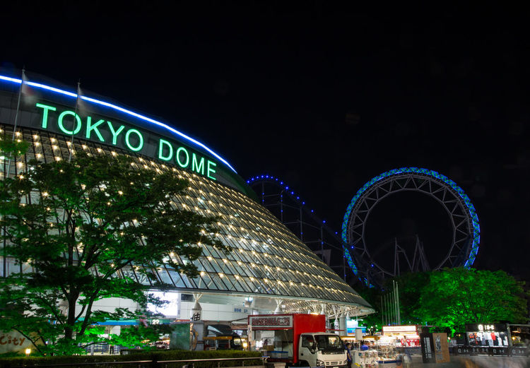 Tokyo Dome at night Tokyo Tokyo Dome Architecture Arts Culture And Entertainment Building Exterior Built Structure City Illuminated Low Angle View Neon Night No People Outdoors Sky Travel Destinations Tree